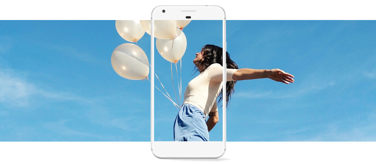 a woman with her arms spread, holding white balloons, with a blue sky in the background, with a Google Pixel phone superimposed over her, as if it's capturing her in its frame as she cries