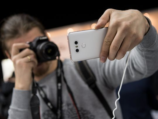 A journalist takes a photo of the new model LG G6 by